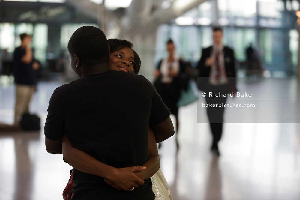 A departing lover hugs her boyfriend farewell before her long-haul flight in the Departures concourse at Heathrow Airport's T5