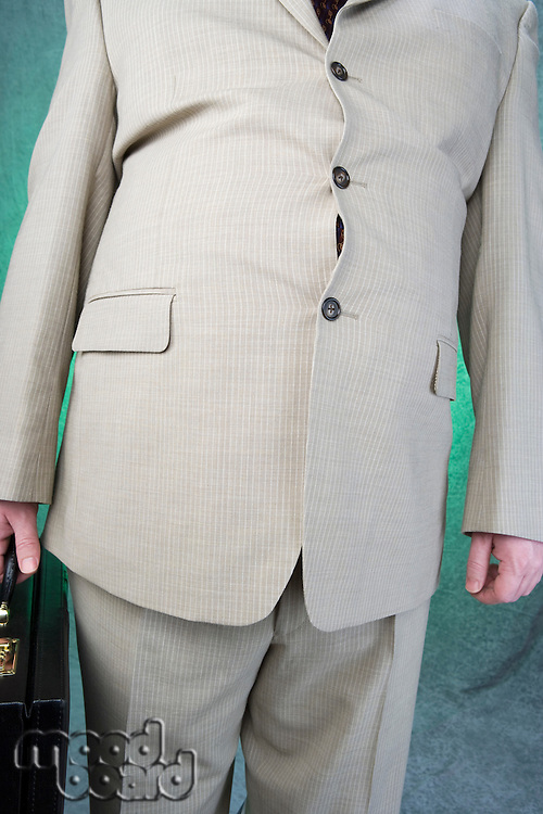 Well-dressed overweight mid-adult man standing and holding briefcase, mid section