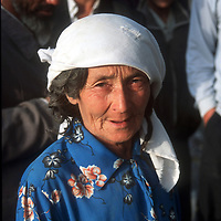 OASIS TOWN ALONG TAKLAMAKHAN DESERT,1 OCTOBER 2001: a elderly Uighur farmer woman stands in a street in a desert village along the Taklamakan desert in southern xinjiang province,china.The living standards in the south of Xinjiang are very basic,the average income is about 50 us/month.. Uighur muslims in southern Xinjiang province lead very basic lifestyles and have an average monthly income of about 50 US$.. (photo by: katharina hesse/Grazia Neri).