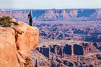 A woman standing at the edge of the canyon taking in the spectacular views. Island In The Sky, Canyonlands National Park, Utah, USA.