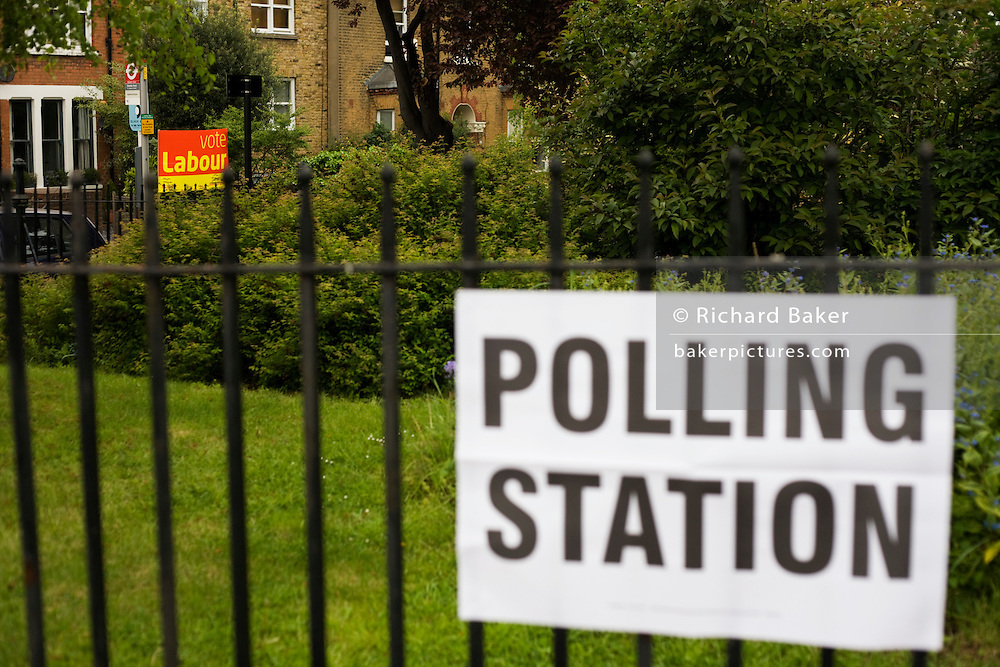 A Labour Party sign is clearly seen at a bus stop opposite St. Saviour's Church, Herne Hill SE24 that serves as a temporary Polling station for voters on Britain's general election day.