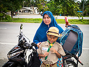 10 JULY 2013 - PATTANI, PATTANI, THAILAND: A Muslim woman with her son, a Thai Boy Scout, on his way to school. Many Muslim parents prefer to send their children to Muslim private schools because they are safer (public schools have been attacked by Muslim insurgents), the Muslim schools teach an Islam centric curriculum and teach what many in Pattani consider a more accurate version of Pattani history.   PHOTO BY JACK KURTZ