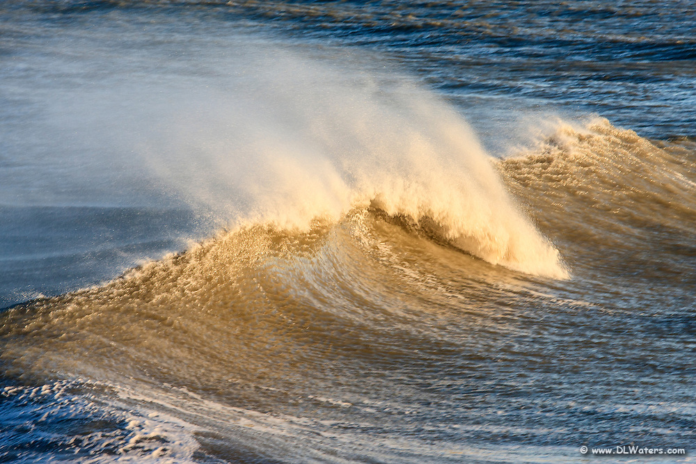 Wind bowing water off the top of a wave at Kitty Hawk Pier.