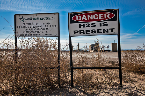 H2S warning sign at an oil and gas operation site in the Permian Basin.