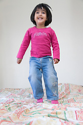 Little girl bouncing on the bed,