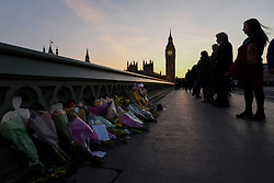 © Licensed to London News Pictures. 24/03/2017. London, UK. Passers by on Westminster Bridge at sunset view floral tributes laid out following the terrorist attack in Westminster where five lost their lives and 40 people were injured.  Photo credit : Stephen Chung/LNP