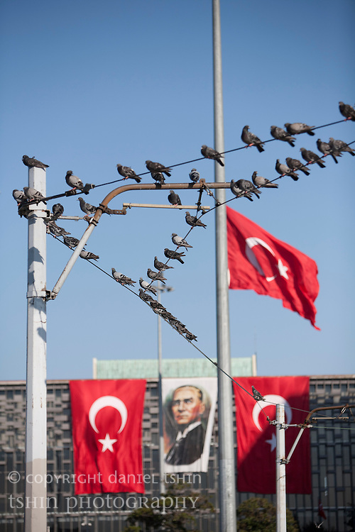Birds sitting on an overhead electrified power line for trams in Taksim Square with the Turkish flag flying in the background.