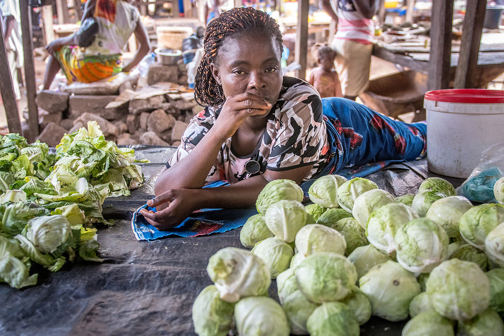 A woman reclines on a table in Ganta, Liberia