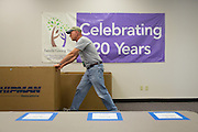 David Bratton-Kearns, COO of the Family Giving Tree, pushes a box of donated backpacks for volunteers to process on Aug. 3, 2012.  Photo by Stan Olszewski/SOSKIphoto.