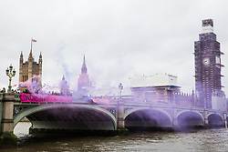 London, UK. 18th December, 2018. Activists from around the UK, accompanied by Jonathan Bartley, co-leader of the Green Party, drop a banner from Westminster Bridge in solidarity with the Stansted 15 and all migrants on International Migrants Day. The Stansted 15 were convicted on 10th December of an anti-terrorism offence under the Aviation and Maritime Security Act 1990 following non-violent direct action to try to prevent a Home Office deportation flight carrying precarious migrants to Nigeria, Ghana and Sierra Leone from taking off from Stansted airport in March 2017. The judge directed the jury to disregard evidence put forward in their defence that their acts were intended to stop human rights abuses.