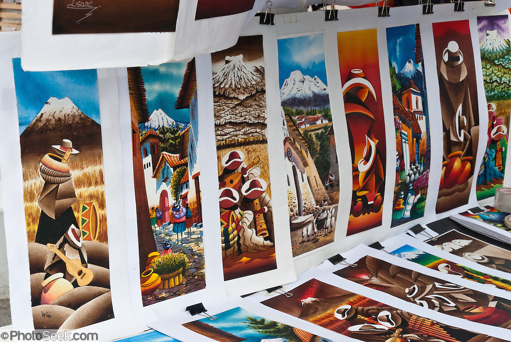 Colorful paintings are sold at Otavalo market, Ecuador, South America. The culturally vibrant town of Otavalo attracts many tourists to a valley of the Imbabura Province of Ecuador, surrounded by the peaks of Imbabura 4,610m, Cotacachi 4,995m, and Mojanda volcanoes. The indigenous Otavaleños are famous for weaving textiles, usually made of wool, which are sold at the famous Saturday market and smaller markets during the rest of the week. The Plaza del Ponchos and many shops tantalize buyers with a wide array of handicrafts. Nearby villages and towns are also famous for particular crafts: Cotacachi, the center of Ecuador's leather industry, is known for its polished calf skins; and San Antonio specializes in wood carving of statues, picture frames and furniture. Otavaliña women traditionally wear distinctive white embroidered blouses, with flared lace sleeves, and black or dark over skirts, with cream or white under skirts. Long hair is tied back with a 3cm band of woven multi colored material, often matching the band which is wound several times around their waists. They usually have many strings of gold beads around their necks, and matching tightly wound long strings of coral beads around each wrist. Men wear white trousers, and dark blue ponchos. Otavalo is also known for its Inca-influenced traditional music (sometimes known as Andean New Age) and musicians who travel around the world.