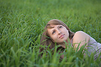 Young woman lies in a field of grass looking up