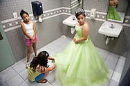 Maria Lopez-Garcia, 15, right, of Lanham, gets dressed in the bathroom of the Langley Park Community Center with her sister, Yesenia Lopez, 11, and mother, Leticia Garcia who wants her three U.S.-born children to have the careers she and her husband didn't have, to get out of poverty and live a comfortable life.  Lopez-Garcia is a legal resident, but her father has had immigration problems and was almost deported several years ago.  Lopez-Garcia celebrated her fifteenth birthday with a group of other Latinas from from low-income immigrant families taking part in a self improvement program.  It ended with a big quinceanera celebration marking the traditional end of childhood for these Hispanic girls.  <br />