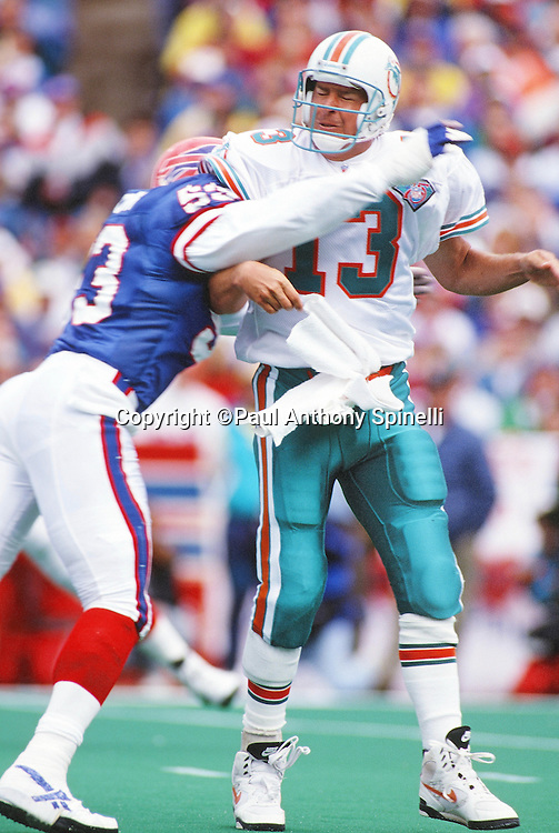 Miami Dolphins quarterback Dan Marino (13) grimaces as he gets hit by Buffalo Bills linebacker Marvcus Patton (53) after throwing a pass during the NFL football game against the Buffalo Bills on Oct. 9, 1994 in Orchard Park, N.Y. The Bills won the game 21-11. (©Paul Anthony Spinelli)