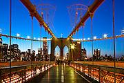 The Brooklyn Bridge at dusk from the pedestrian walkway, facing Manhattan.