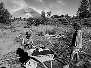 23 JANUARY 2018 - DARAGA, ALBAY, PHILIPPINES: Men mine black volcanic sand and gravel in an ancient lava flow while the Mayon volcano erupts in the background. Mayon is the most active volcano in the Philippines and its eruptions in January 2018 shut down most of Albay province and triggered the evacuation of almost 80,000 people.      PHOTO BY JACK KURTZ