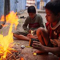 Lighting a fire in the street to roast corn