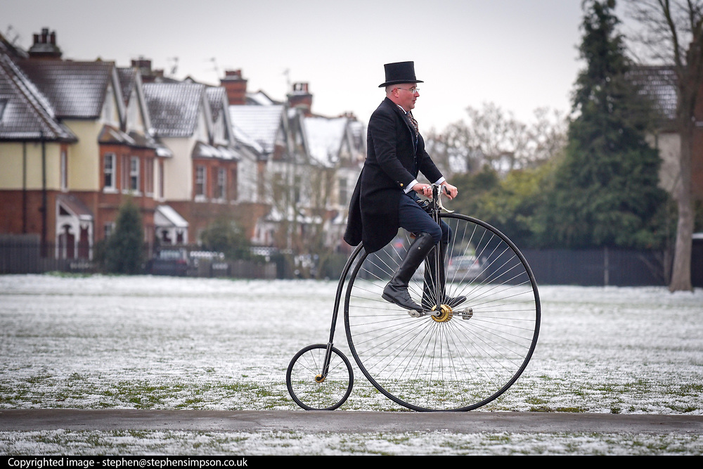 &copy; Licensed to London News Pictures. 18,03,2018. Surbiton, UK.  <br /> Families enjoy riding Penny Farthings in the snow in Surbiton today 18 March 2018. Locals were taking part in a project celebrating the Penny Farthing&rsquo;s maker, one time Surbiton resident and carpenter's apprentice John Keen, who became one of the most important pioneering figures in cycling history. He quit his carpentry career and dedicated himself to becoming the undisputed &quot;boneshaker&quot; racing champion of Britain. He could ride half a mile in 2 min 45 secs. Keen realised the &quot;boneshaker&quot; was heavy and cumbersome in design and went on to build something better - the &quot;ordinary bicycle&quot; - which later became known at the &quot;penny farthing&quot; Known as Happy Jack, Keen raced until he was 36, but his health failed and he faded into obscurity. He died in 1902.  Photo credit: Stephen Simpson/LNP