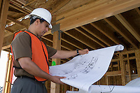 Construction worker observing half constructed house while holding blueprints