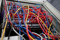 Low angle of tangled wires in server room at television station