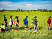 09 OCTOBER 2016 - JEMBRANA, BALI, INDONESIA: Spectators walk through a rice field on their way to a makepung (buffalo race) in Tuwed, Jembrana, Bali. Makepung is buffalo racing in the district of Jembrana, on the west end of Bali. The Makepung season starts in July and ends in November. A man sitting in a small cart drives a pair of buffalo bulls around a track cut through rice fields in the district. It's a popular local past time that draws spectators from across western Bali.     PHOTO BY JACK KURTZ