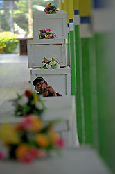 A man sits near coffins of victims of AirAsia Flight QZ8501 at a hospital in Pangkalan Bun, Indonesia. Jan. 4, 2015. An Indonesian pilot taking part in the multinational search operation said here on Sunday that three more bodies were found in AirAsia crash site off Borneo coast. EXPA Pictures © 2015, PhotoCredit: EXPA/ Photoshot/ Agung Kuncahya B.<br /> <br /> *****ATTENTION - for AUT, SLO, CRO, SRB, BIH, MAZ only*****