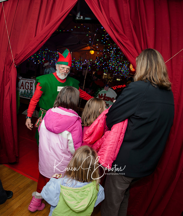 Twinkle the Elf opens the door of the Christmas elevator as he brings children into the magic of the annual Christmas Village on Thursday evening.  (Karen Bobotas/for the Laconia Daily Sun)