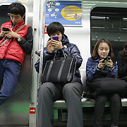 South Korean commuters using their mobile phones while traveling on the Seoul Metropolitan Subway, Seoul, South Korea. 22nd March 2012. Photo Tim Clayton