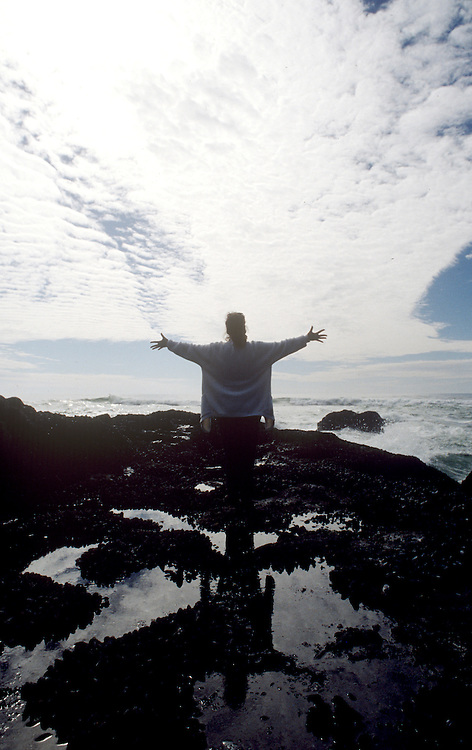 The slihouette of a woman with her arms spread out to the Pacific Ocean embracing sea and sky from the Pacific Northwest's rocky coastline in Oregon. A small tidepool is under her feet and she is expressing awe, joy, and happieness at the wonders of nature. A streaming bank of clouds against the blue sky seems to disappear into the horizon where the sky and ocean meet.