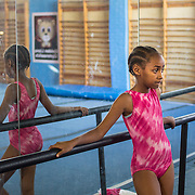 A young gymnast is watching her friends perform their routine at the Golden Lions Gymnastics Club in Newlands, Johannesburg. © Miora Rajaonary