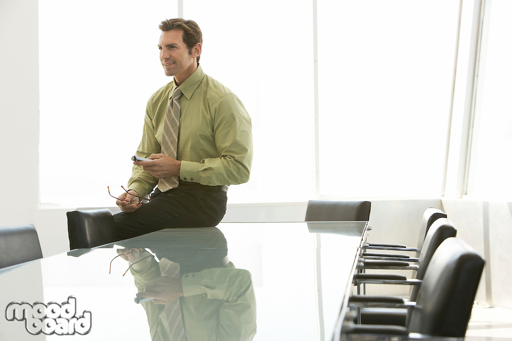 Businessman using remote control in conference room