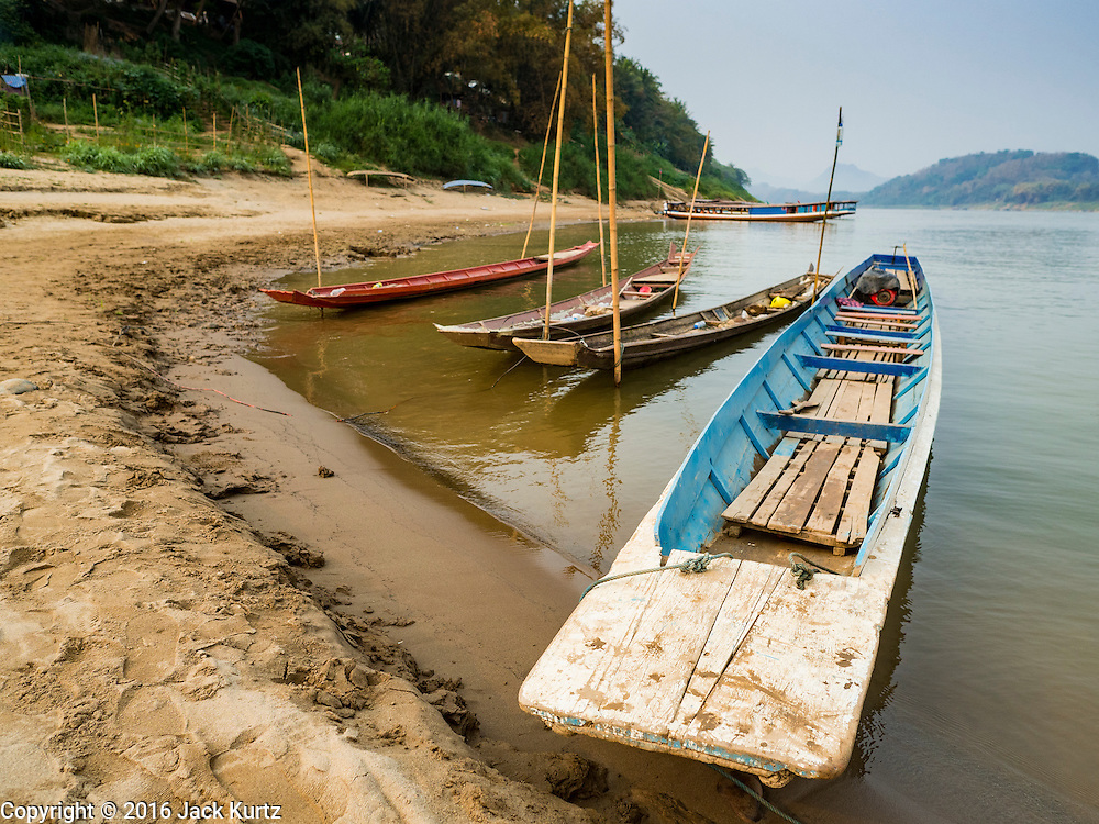 12 MARCH 2016 - LUANG PRABANG, LAOS:  Passenger boats tied up on the bank of the Mekong River near Luang Prabang. Laos is one of the poorest countries in Southeast Asia. Tourism and hydroelectric dams along the rivers that run through the country are driving the legal economy.      PHOTO BY JACK KURTZ