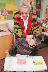 Teacher assisting young boy with a physical impairment; a wheelchair user; to paint using adapted head gear,