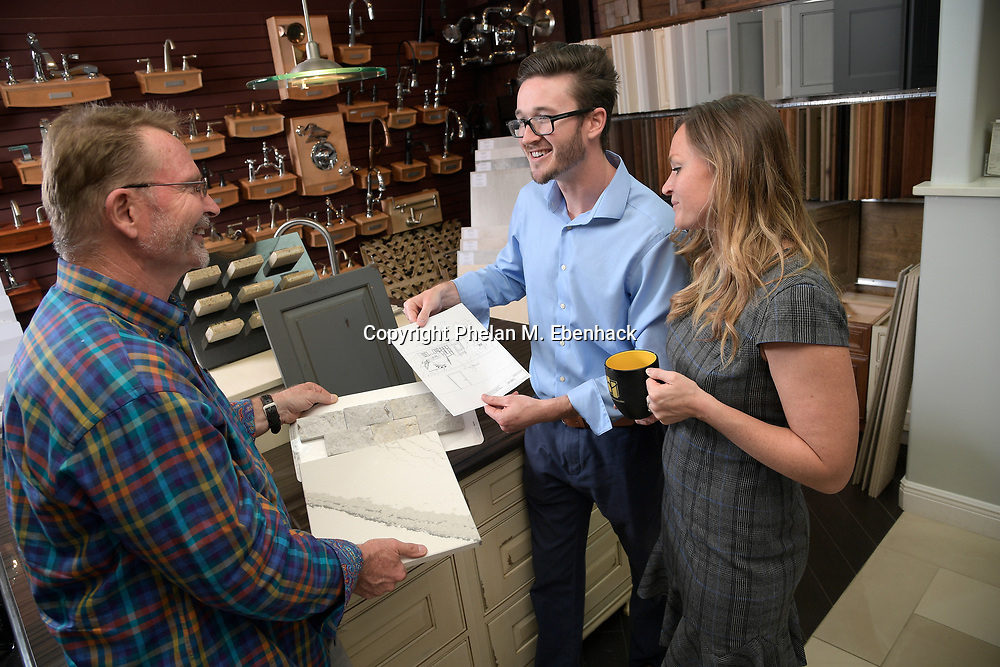 Keith Vellequette, left, owner and lead designer of KBF Design Gallery, talks about a project with family members Ashley, right, and Adam at their showroom Monday, Sept. 18, 2017, in Altamonte Springs, Fla. (Photo by Phelan M. Ebenhack)