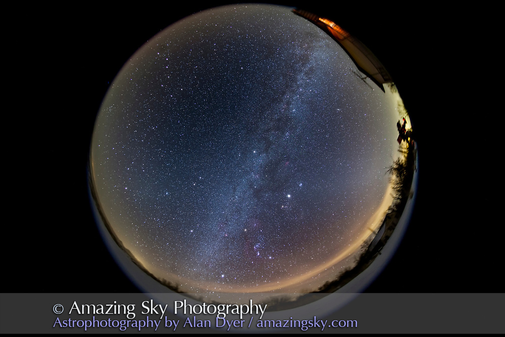 The northern winter sky in a 360° fish-eye view from my backyard, Feb. 7, 2013, on a partly hazy night with some clouds reflecting light pollution from sodium vapour highway and street lights. This is a stack of 8 x 4 minute exposures but the foreground is from just one exposure. All with the 8mm Sigma fish-eye lens at f/4 and Canon 5D MkII at ISO 800. Jupiter is the brightest object. The Zodiacal Light reaches up from the west at right and goes across the sky to form the Gegenschein, a subtle bright patch below centre at left in Cancer and Leo. A telescope taking close up shots of Orion is silhouetted against the distant sky glow at right.