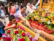 "05 JULY 2014 - BANGKOK, THAILAND: Thais donate money to a float during a parade for vassa. Vassa, called ""phansa"" in Thai, marks the beginning of the three months long Buddhist rains retreat when monks and novices stay in the temple for periods of intense meditation. Vassa officially starts July 11 but temples across Bangkok are holding events to mark the holiday all week.    PHOTO BY JACK KURTZ"