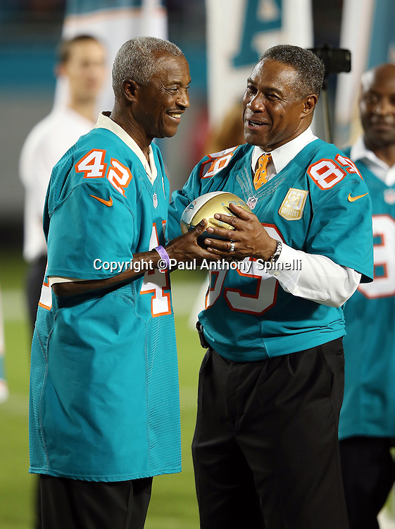 Former Miami Dolphins wide receiver Paul Warfield (left) smiles as he is given a token football by former Miami Dolphins wide receiver Nat Moore during a halftime ceremony honoring the 50 all-time Dolphin great players during the Miami Dolphins NFL week 14 regular season football game against the New York Giants on Monday, Dec. 14, 2015 in Miami Gardens, Fla. The Giants won the game 31-24. (©Paul Anthony Spinelli)