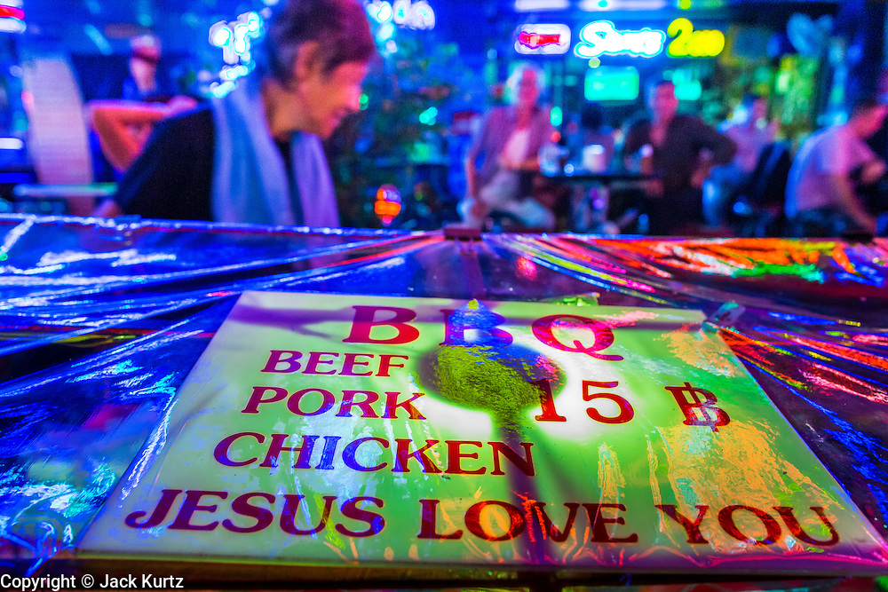 "19 JANUARY 2013 - BANGKOK, THAILAND:  A vendor sells barbecued meat on Soi Cowboy, a red light district in Bangkok. The bottom of his menu says ""Jesus Loves You."" Prostitution in Thailand is technically illegal, although in practice it is tolerated and partly regulated. Prostitution is practiced openly throughout the country. The number of prostitutes is difficult to determine, estimates vary widely. Since the Vietnam War, Thailand has gained international notoriety among travelers from many countries as a sex tourism destination. One estimate published in 2003 placed the trade at US$ 4.3 billion per year or about three percent of the Thai economy. It has been suggested that at least 10% of tourist dollars may be spent on the sex trade. According to a 2001 report by the World Health Organisation: ""There are between 150,000 and 200,000 sex workers (in Thailand).""       PHOTO BY JACK KURTZ"
