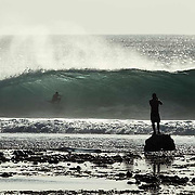 A Surfer takes a photo of another surfer riding a barrel at Desert Point, Lombok, Indoens.a