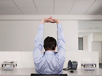 Male office worker stretching at desk
