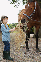 Girl (5-6) feeding horse hay outdoors