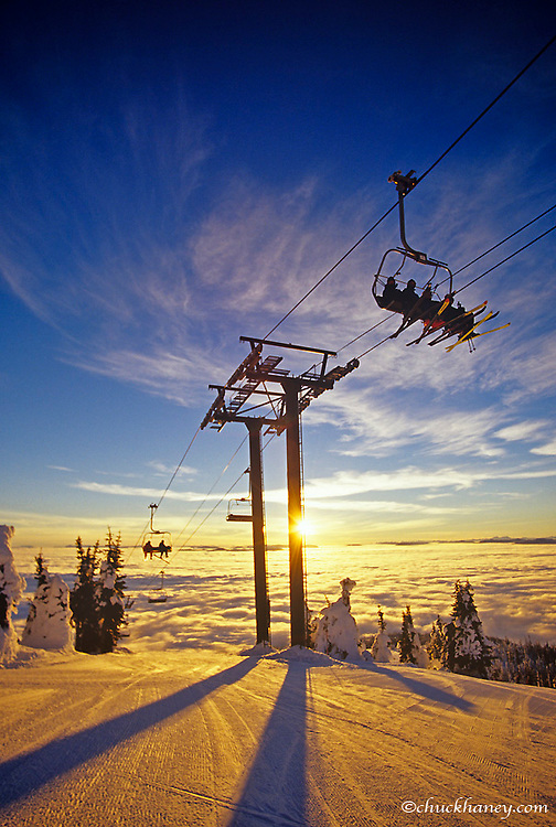 Chairlift carries riders up for last run at sunset above the inversion clouds at Whitefish Mountain Resort in Montana