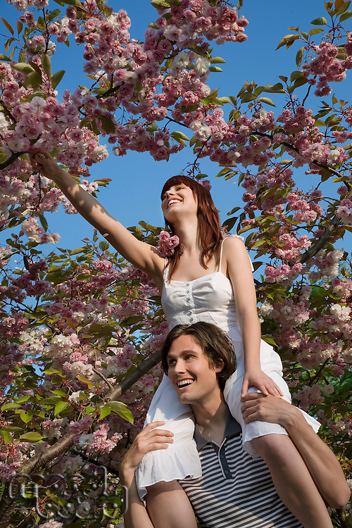 Young Man Lifting Woman up to Tree Branch