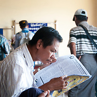 Myanmar (Burma). Yangon. A man reads a newspaper whilst waiting for a ferry.