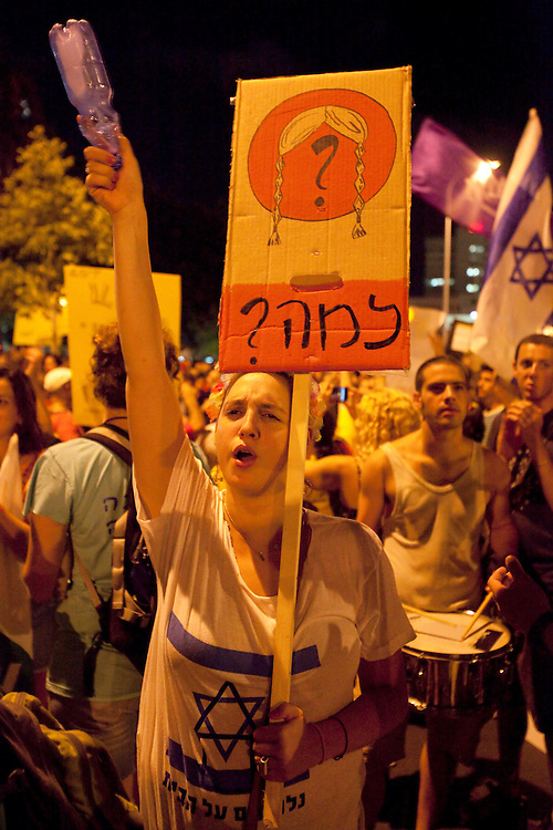 An Israeli protestor holding a signboard asking &quot;why?&quot; as her way to emphasize the peoples' nai'vet&eacute; facing an exploited government, during the massive demonstration against the rising cost of living in Israel. Tel-Aviv, Aug. 6, 2011.<br /> <br /> <br /> At least a courter of million Israelis marched in a protest against the rising cost of living in Israel, in central Tel Aviv, Saturday, Aug. 6, 2011. The Israeli citizens are furious over the worsening social conditions in the country due to the increasing pricing of housing, taxes and basic products and also protesting over the lack of social welfare. Israelis poured en masse into the streets of major cities on Saturday night in a massive demonstration. Thousands of mostly middle class Israelis marched through the streets of the city waving flags, beating drums and shouting: &quot;The people demand social justice&quot;.
