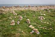 Piles of stones and rocks in the coastal landscape on Holy Island, on 27th September 2017, on Lindisfarne Island, Northumberland, England. The Holy Island of Lindisfarne, also known simply as Holy Island, is an island off the northeast coast of England. Holy Island has a recorded history from the 6th century AD; it was an important centre of Celtic and Anglo-saxon Christianity. After the Viking invasions and the Norman conquest of England, a priory was reestablished.