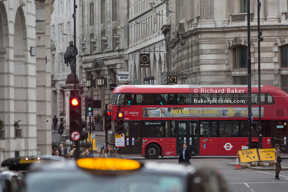 A red London Routemaster bus crosses the junction at Bank, in the City of London, the capital's financial district (aka The Square Mile), on 26th March, 2018, in London, England.