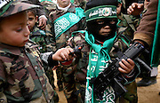 .A Young  Palestinian boy dressed as a Hamas militant holds two toy guns with other small boys wearing military uniforms bearing Hamas banners during a rally  celebrating Hamas's victory in the Palestinain  parliamentary elections held at the Jabalya refugee camp.