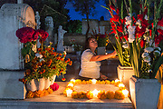 A Mexican woman lights candles at the gravesite of relatives for Day of the Dead festival known in Spanish as Día de Muertos at the old cemetery October 31, 2013 in Xoxocotlan, Mexico. The festival celebrates the lives of those that died.
