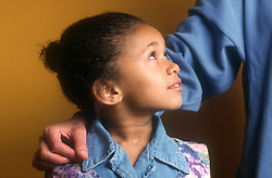 Side profile of young girl looking up at adult who has arm around her shoulder,